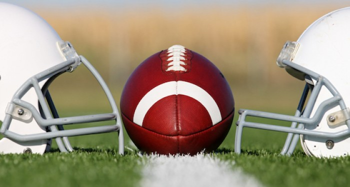 American football placed between two football helmets on field
