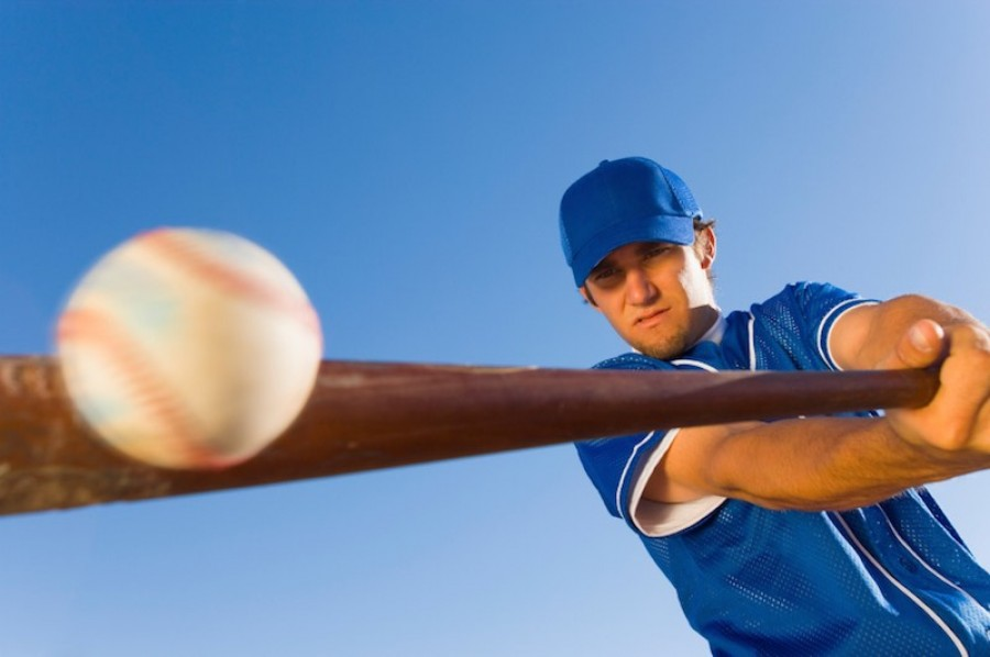 Baseball player hitting the ball with a bat