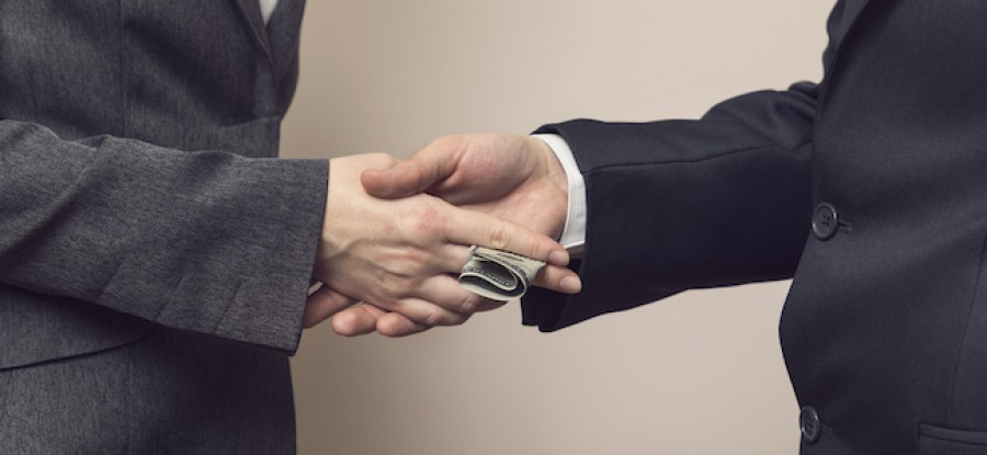 Bribe being expected with a handshake