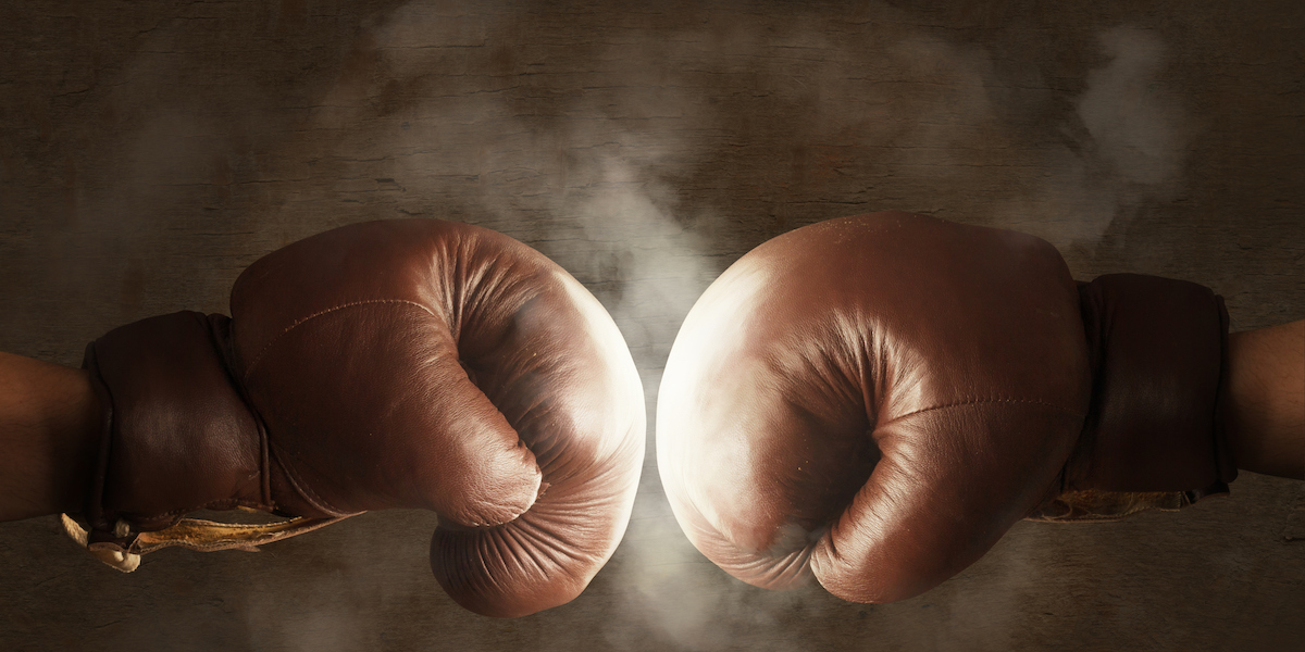 Brown boxing gloves hitting each other