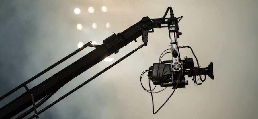 Camera suspended above sports field in front of floodlights
