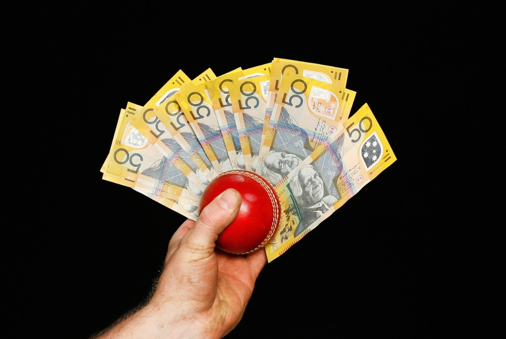 Cash and Cricket Ball In Hand