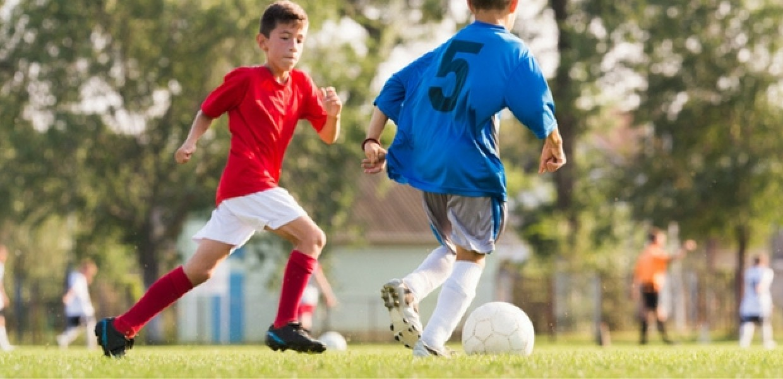 Children playing football on grass