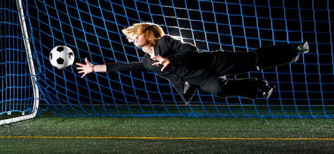 Female football player diving for ball in suit