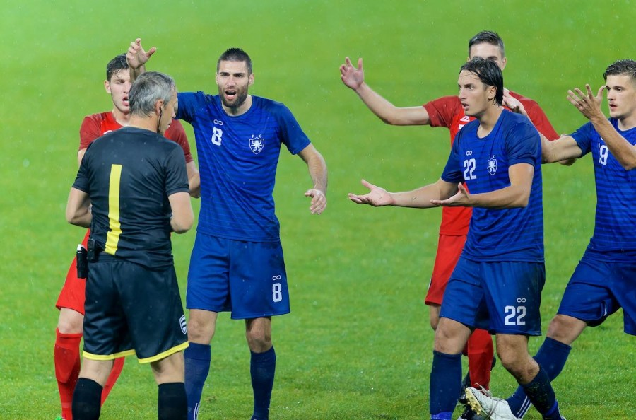 Image of football players arguing with referee