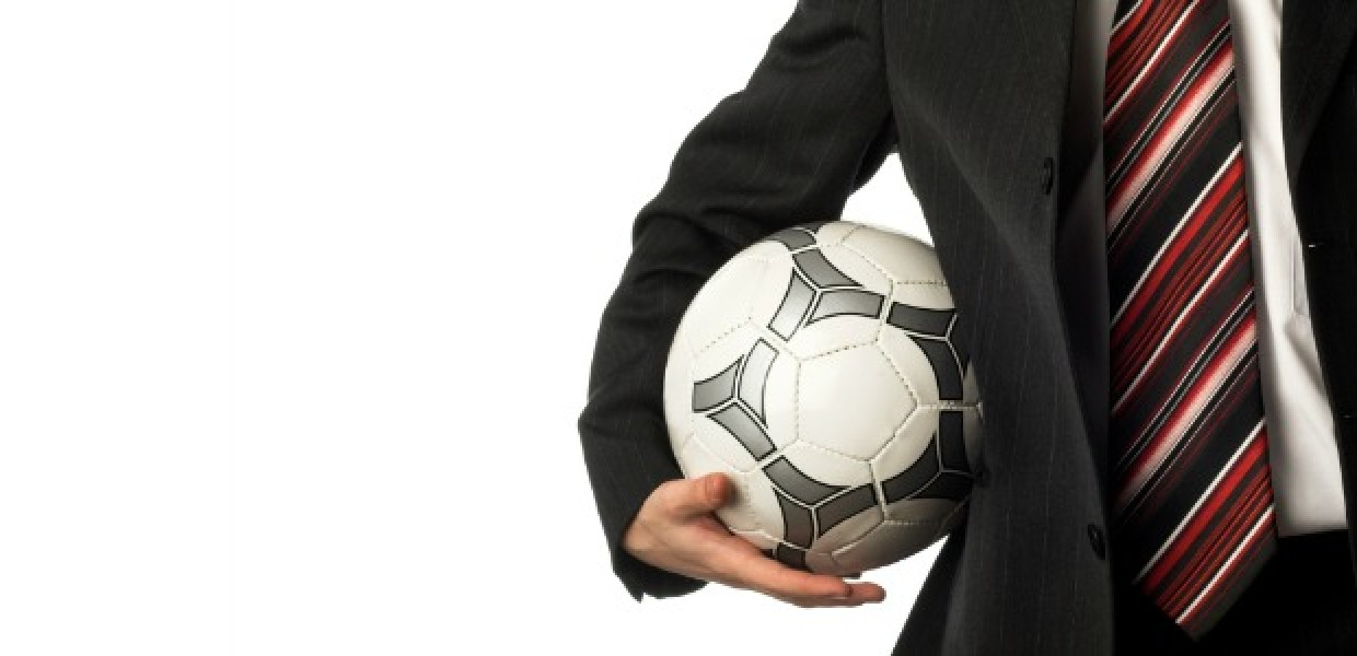 Football being carried by man in suit