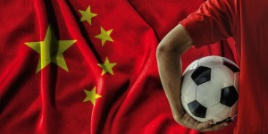 Football player holding football in front on the national flag of China