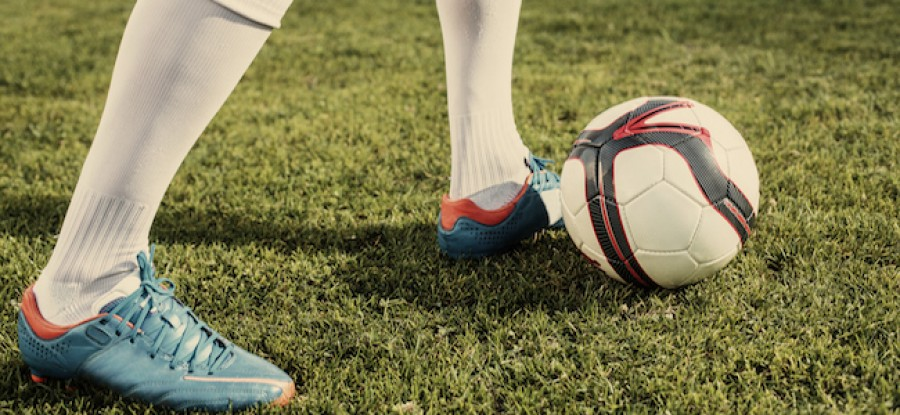 Football cleats and ball on grass