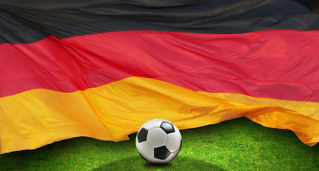 Football on grass in front of German flag