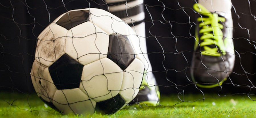 Football inside of goal in front of player
