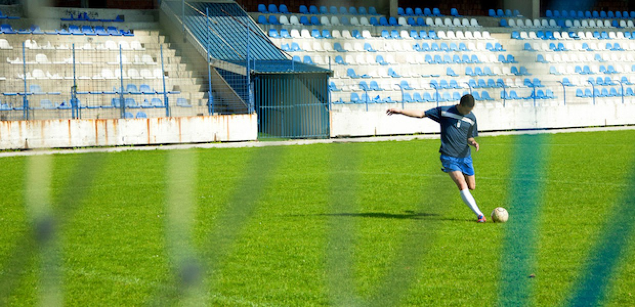 Footballer in training shooting at the goal