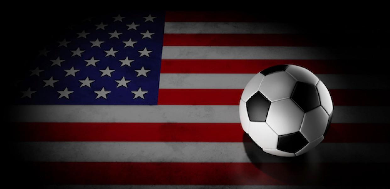 Football on American flag under spotlight