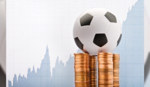 Football on coins in front of graph