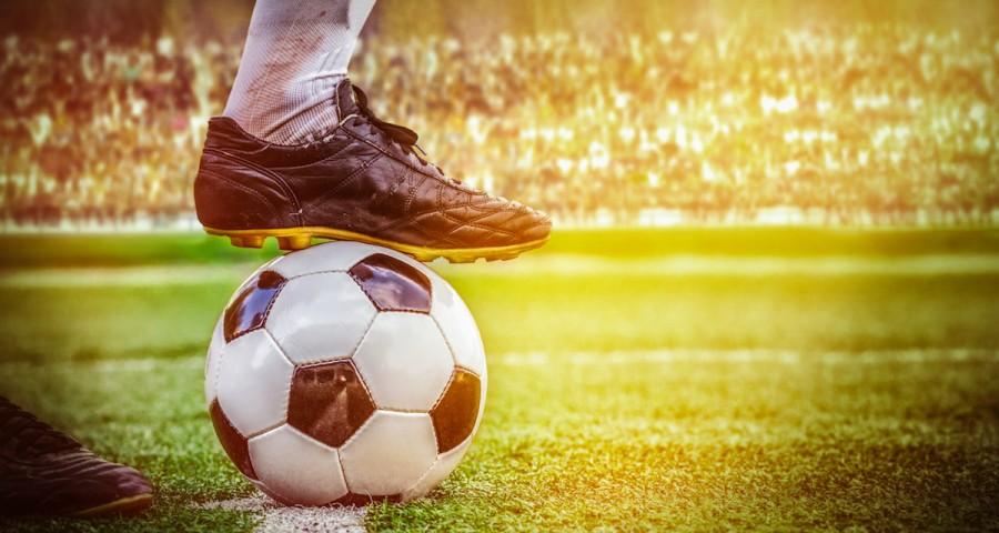 Footballer and football on field