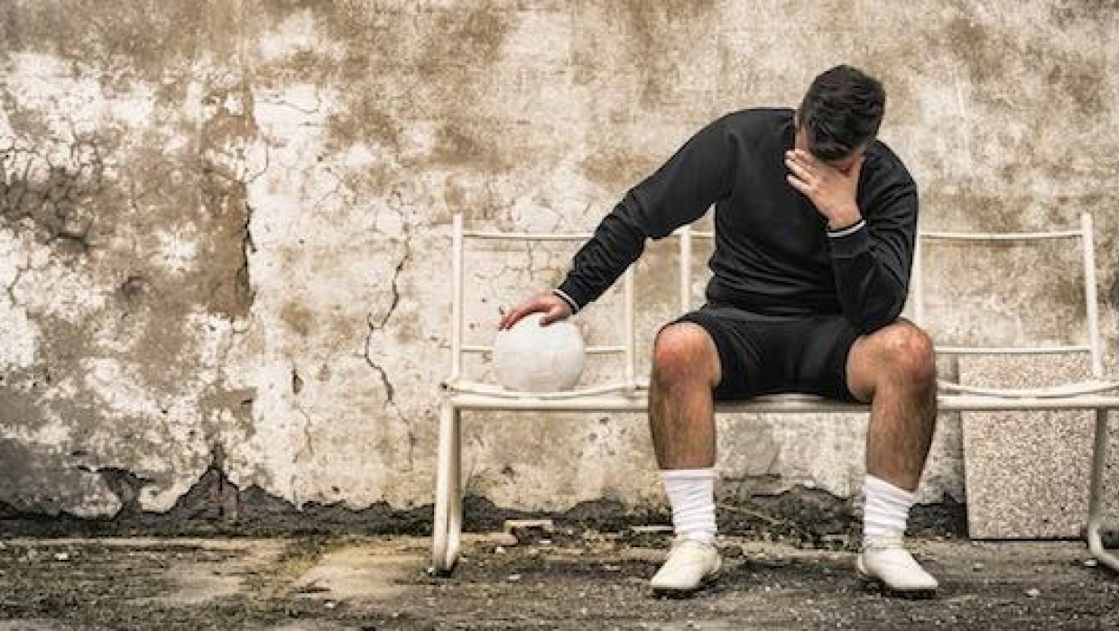 Football player disappointed on bench
