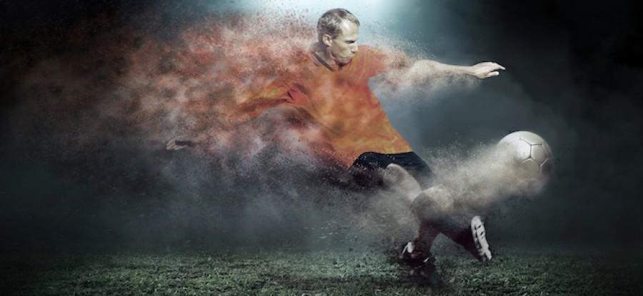 Football player kicking ball on grass