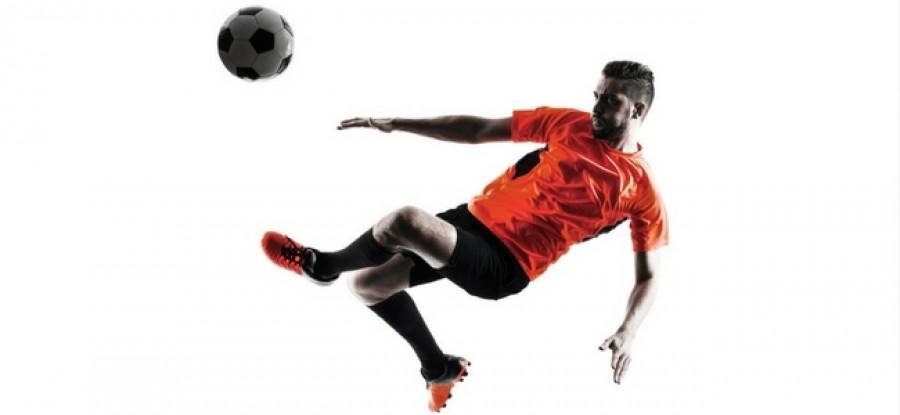 Football player mid air to kick ball