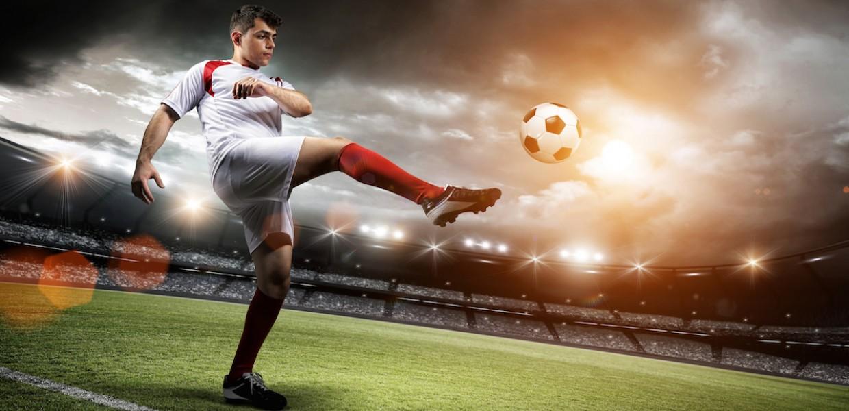 Football player on field kicking ball