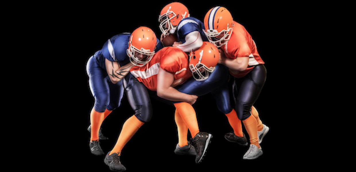 Football players in the middle of a tackle