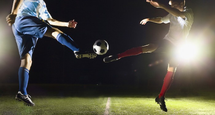 Football players mid air under floodlights