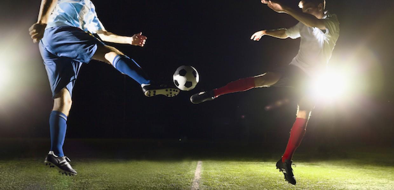 Football players mid air under floodlights