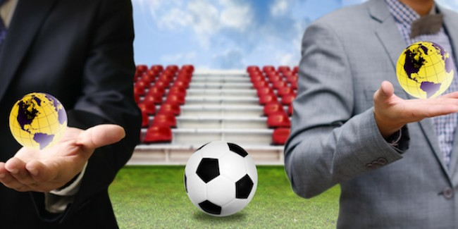 Global football with businessman holding small globes with football in between