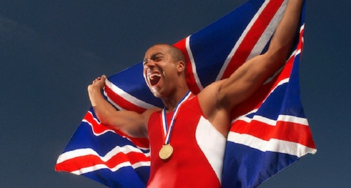 Gold medalist holding a UK flag behind him