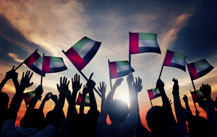 Group of people waving UAE flag