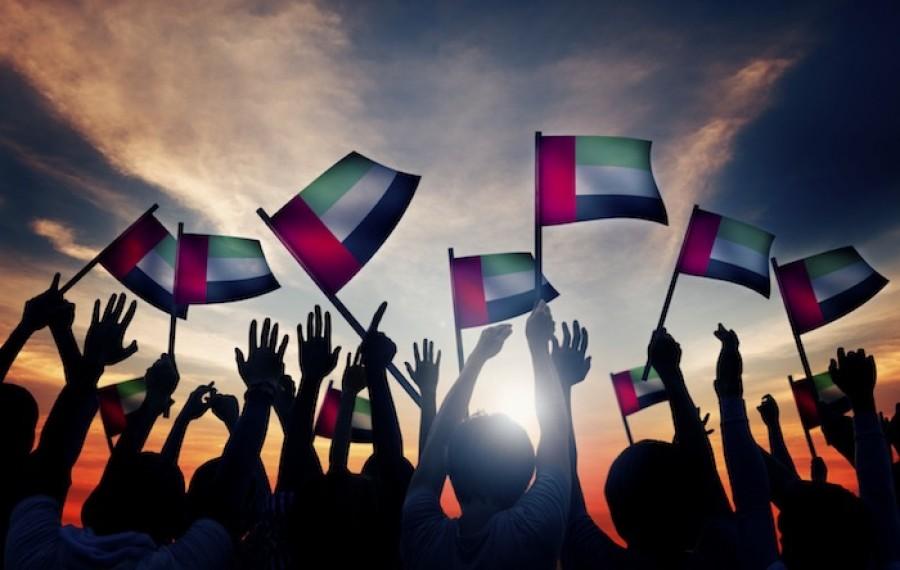 Group of people waving UAE flag