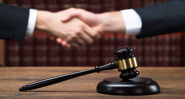 Handshake by a gavel on the table