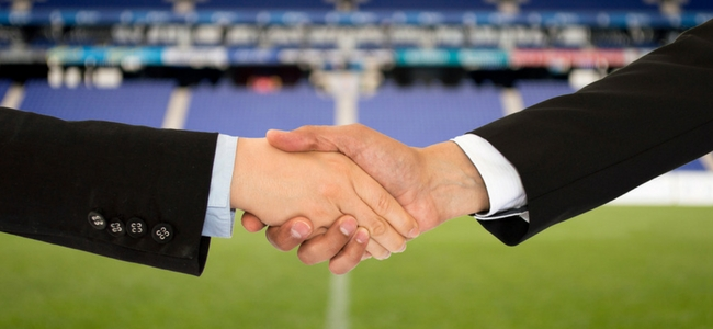 Handshake with football field in background