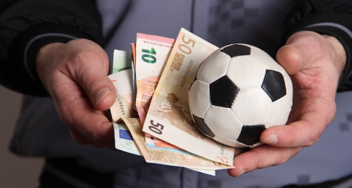 Man holding football and money in his hands