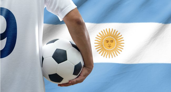 Player_Holding_Football_in_front_of_Argentinian_Flag