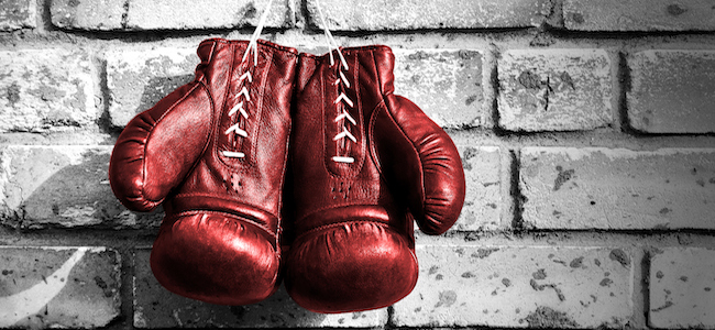 Red boxing gloves hanging on brick wall