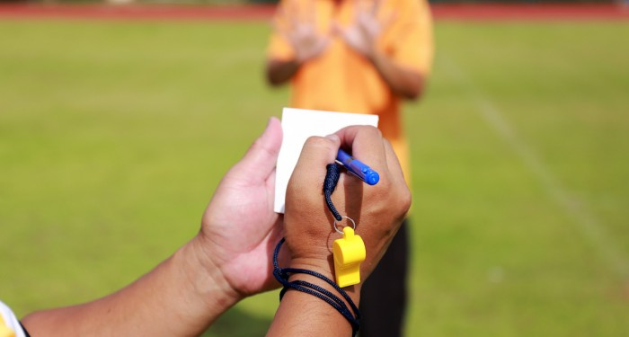 Referee writing on notepad