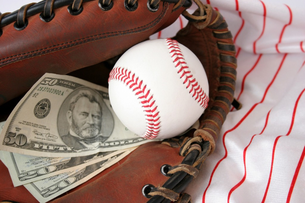 Baseball glove holding a ball and cash