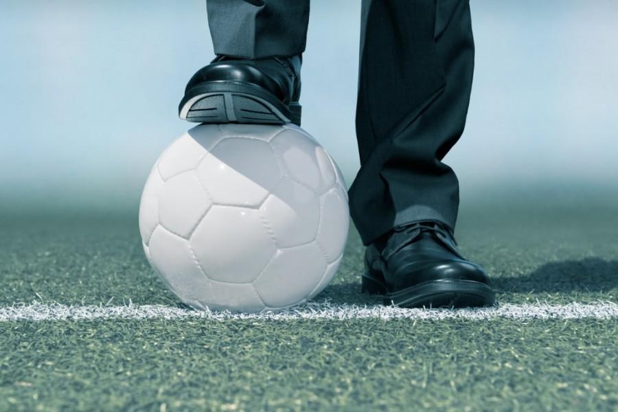 Business man standing on a football