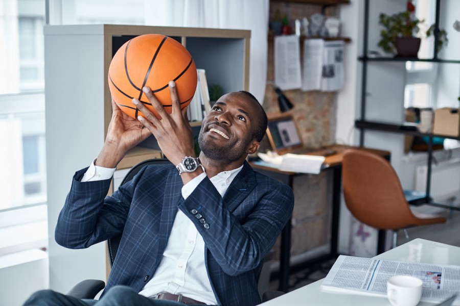 Businessman throwing basketball in the air at his desk.