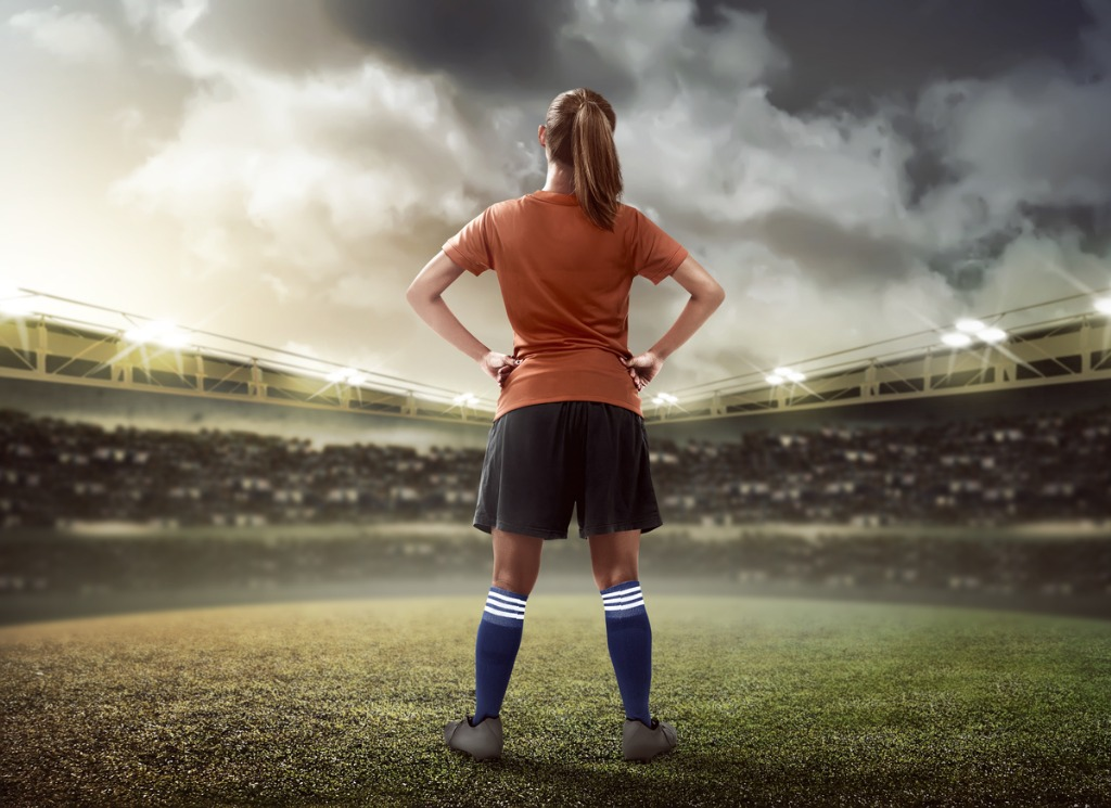 Female Footballer Standing on Pitch