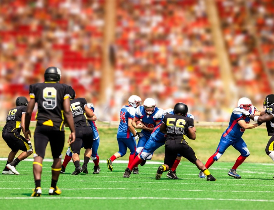 American football running back carrying ball through defenders
