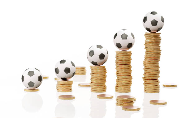 Football stacked on piles of money