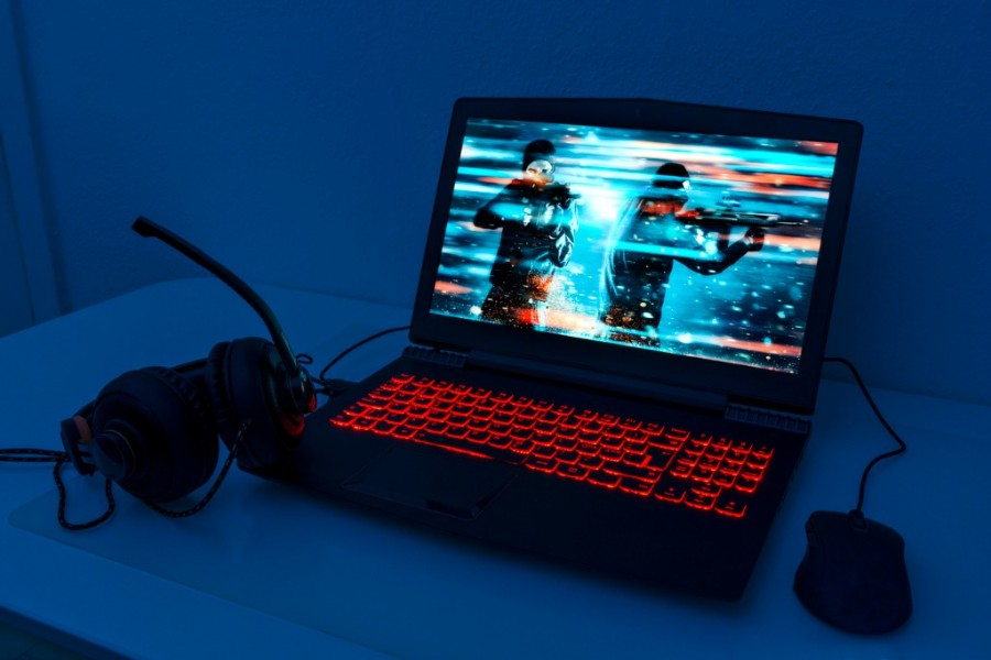 Gaming Laptop With Mouse and Headphones and Image Of A Game With Two Men With Guns On Screen