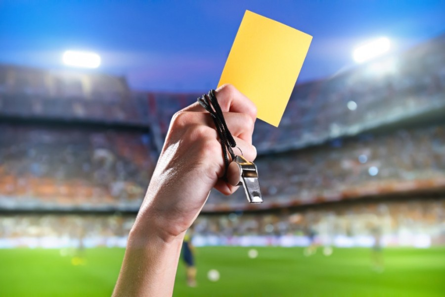 Hand of A Referee With Yellow Card and Whistle