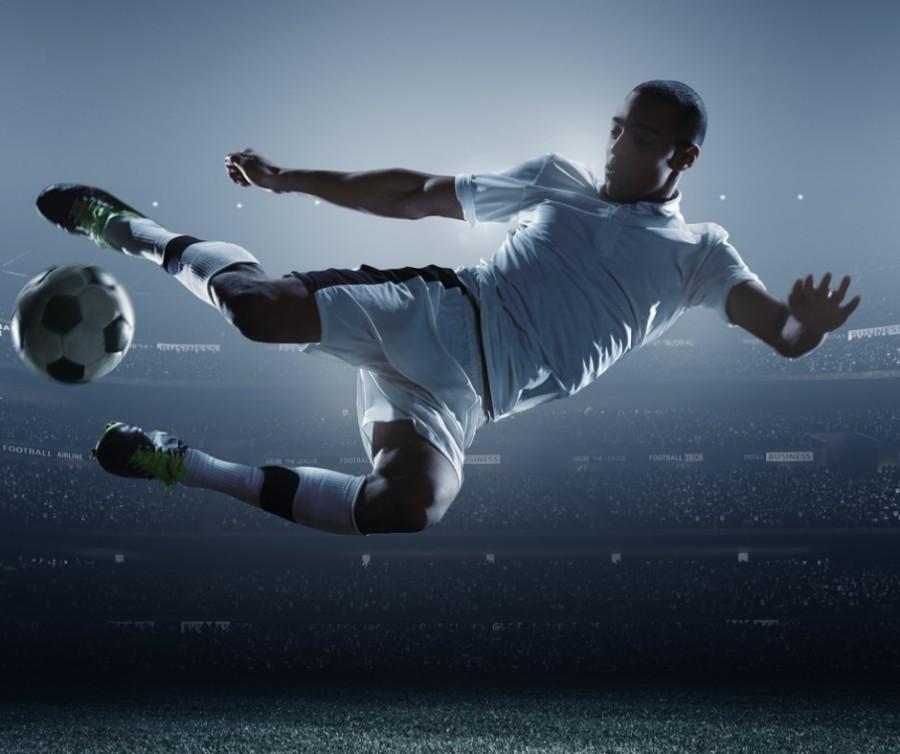 Footballer Kicking Ball In Stadium
